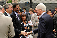 Former President Bill Clinton shakes hands with David Downs and Ed Foster-Simeon prior to a press conference announcing former President Bill Clinton as the honorary chairman of the USA Bid Committee to host the FIFIA World Cup in 2018 or 2022 at the FC Harlem Field in Harlem, NY, on May 17, 2010.