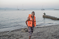 Syrian refugee taking a bath with his life jacket.He has been sleeeping in the street for more than a week waiting for the paper from the police to go to Athens.  Kos, Greece. Sept. 5, 2015