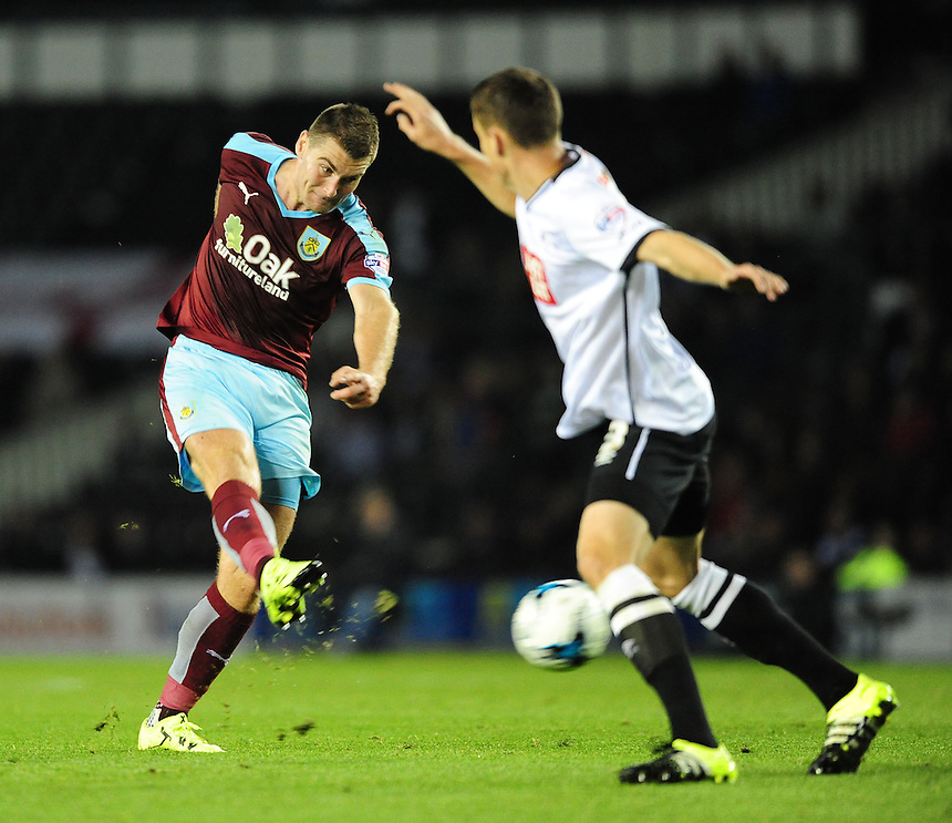 Burnley's Sam Vokes hits a shot towards goal under pressure from Derby County's Craig Forsyth<br /> <br /> Photographer Chris Vaughan/CameraSport<br /> <br /> Football - The Football League Sky Bet Championship - Derby County v Burnley - Monday 21st September 2015 - iPro Stadium - Derby<br /> <br /> &copy; CameraSport - 43 Linden Ave. Countesthorpe. Leicester. England. LE8 5PG - Tel: +44 (0) 116 277 4147 - admin@camerasport.com - www.camerasport.com