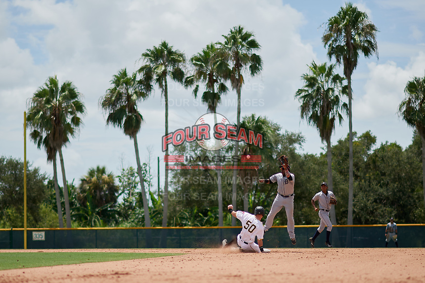 GCL Tigers West second baseman Hector Martinez (4) jumps to receive a throw from the catcher as GCL Pirates Patrick Dorrian (50) slides into second base during a game against the GCL Pirates on August 13, 2018 at Pirate City Complex in Bradenton, Florida.  GCL Tigers West defeated GCL Pirates 5-1.  (Mike Janes/Four Seam Images)