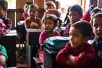 Aastha Baniya (6, in pink) sits with other students in the temporary shed in which her school is running in Chautara, Sindhupalchowk, Nepal on 29 June 2015. Aastha (6) was buried under the rubble together with her mother but Aastha survived while her mother died on the spot. As their father Ratna Baniya (28) cannot care for the three young children on his own, SOS Childrens Villages has since been supporting the grandmother with financial and social support so that she can manage to raise the children comfortably and ensure that they will all be schooled. Photo by Suzanne Lee for SOS Children's Villages