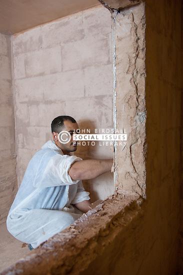 A prisoner learning the plastering trade in a workshop