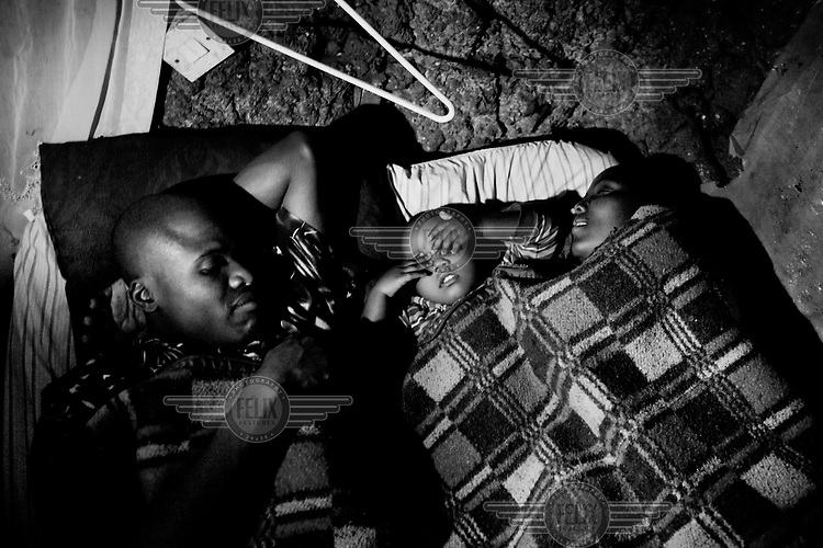 Augustin Odongo and Clarissa in bed with two year old Michelle between them in their home in Kibera.