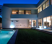 View of the rear of the modern house illuminated at dusk and seen from across the lawn and swimming pool