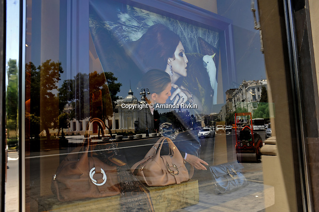 A saleswoman adjusts the window display at Bulgari on Neftciler Prospekt, or Oil Workers' Boulevard, in downtown Baku, Azerbaijan on July 2, 2010.  Luxury shopping in downtown Baku is one symptom of the city within the city or the country within the country where the elite, estimated at 50,000, control much of the country's income and profit from oil revenues, leaving a wide gap in the absence of a middle class between them and the rest of the country.