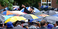 Joshua Abraham says hello to friends amidst a sea of umbrellas as constant rain fell over the graduation ceremony for the University of Virginia Sunday May 18, 2003 in Charlottesville, VA. (Photo/Andrew Shurtleff)