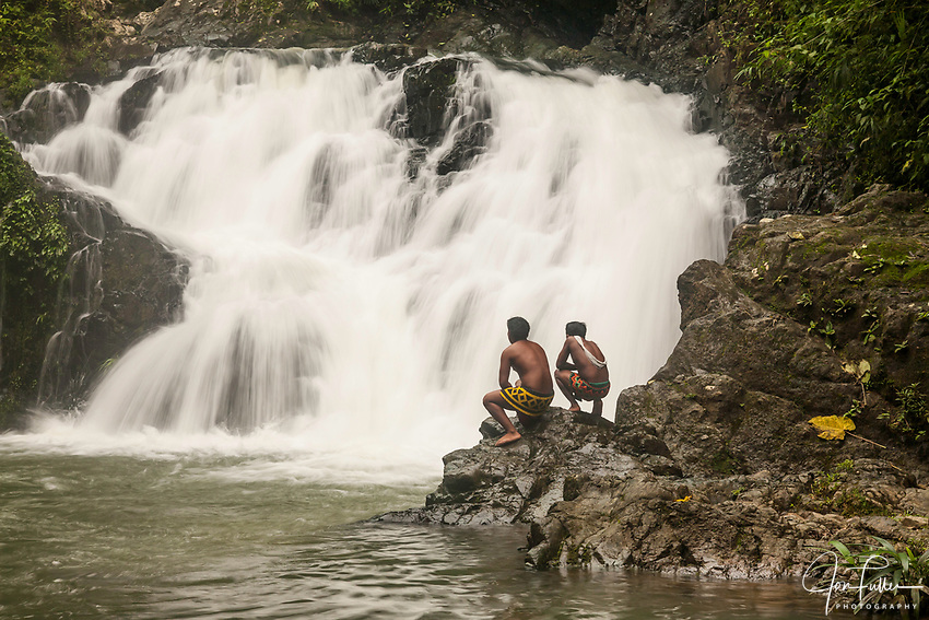 Two young indigenous Embera men in traditional dress stand by a waterfall on the Chagres River in Panama. Chagres National Park
