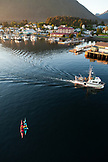 USA, Alaska, Sitka, kayakers take a rest in Sitka Harbor while a fishing boat passes by
