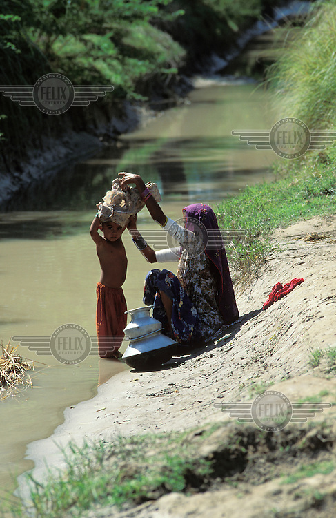 Washing pots and child in the Indus river.
