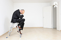 Depressed businessman in empty room, door open (Licence this image exclusively with Getty: http://www.gettyimages.com/detail/103933316 )