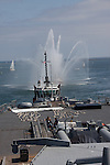 Tugboats provide power and LA City Fire Boats provide fanfare fountains for the final voyage of the battleship USS Iowa from Berth 51 to its new home at Berth 87 in San Pedro, Los Angeles, CA where it opens as a museum ship in July 2012.