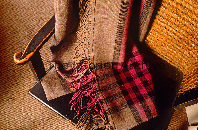 A checked woollen throw graces an antique cane-backed chair placed on a contemporary herringbone jute floor covering