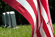 Old weathered headstones in an scenic New England graveyard. American flag