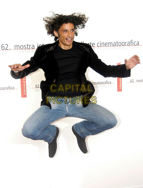 "ENRICO LO VERSO.Photocall of the film ""The fine art of Love"",.62nd International Film Festival,.Venice, 31st August 2005.full length black t-shirt jacket denim jeans jump jumping legs arms hair.www.capitalpictures.com.sales@capitalpictures.com.© Capital Pictures."