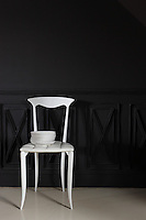 In the dining room the black papier mache panelling is by Les Farfelus Farfadets and the white chair is a Fazem design