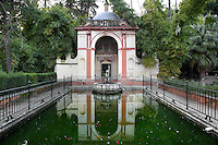 Low angle view of pool, Gardens, Real Alcazar, Seville, Spain, pictured on December 26, 2006, in the afternoon. The Real Alacazar was commissioned by Pedro I of Castile in 1364 to be built in the Mudejar style by Moorish craftsmen. The palace, built on the site of an earlier Moorish palace, is a stunning example of the style and a UNESCO World Heritage site. A domed pavilion and fountain with statue are reflected in the green water of the rectangular pool. Picture by Manuel Cohen.