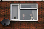 © Joel Goodman - 07973 332324 . 20/01/2018. Doncaster, UK. Children look out of a first floor window as far-right street protest movement , the English Defence League ( EDL ) , hold a demonstration , opposed by anti-fascists , including Unite Against Fascism ( UAF ) in a park in Hexthorpe in Doncaster . EDL supporters chanted anti-Roma slogans as they marched through the town . Photo credit : Joel Goodman