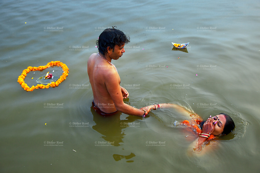 India. Uttar Pradesh state. Allahabad. Maha Kumbh Mela. An Indian Hindu devotee couple takes a holy dip in Sangam. The Kumbh Mela, believed to be the largest religious gathering is held every 12 years on the banks of the 'Sangam'- the confluence of the holy rivers Ganga, Yamuna and the mythical Saraswati. In 2013, it is estimated that nearly 80 million devotees took a bath in the water of the holy river Ganges. The belief is that bathing and taking a holy dip will wash and free one from all the past sins, get salvation and paves the way for Moksha (meaning liberation from the cycle of Life, Death and Rebirth). Bathing in the holy waters of Ganga is believed to be most auspicious at the time of Kumbh Mela, because the water is charged with positive healing effects and enhanced with electromagnetic radiations of the Sun, Moon and Jupiter. The Maha (great) Kumbh Mela, which comes after 12 Purna Kumbh Mela, or 144 years, is always held at Allahabad. Uttar Pradesh (abbreviated U.P.) is a state located in northern India. 6.02.13 © 2013 Didier Ruef