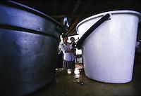 ITALIA Torino  Campo nomadi Rom  (Campo dell'Arrivore, 2001), una donna tiene in braccio una bambina. In primo piano due secchielli