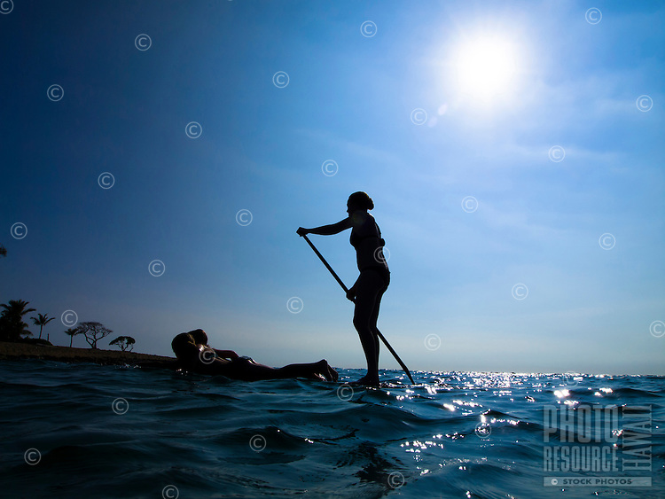 A mother standup paddleboards her two young girls around the sunlit waters of Mahai'ula Bay, Big Island.