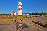 lighthouse reflected in pool on Gulf of St. Lawrence<br /> Pointe des Monts<br /> Quebec<br /> Canada