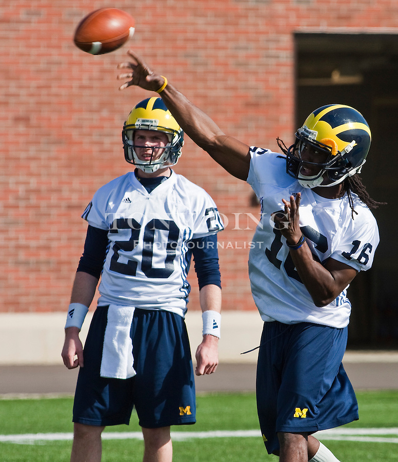 Michigan quarterback Jack Kennedy watches Denard Robinson (16) throw a pass on the first day of spring football practices, Tuesday, March 16, 2010, in Ann Arbor, Mich. (AP Photo/Tony Ding)