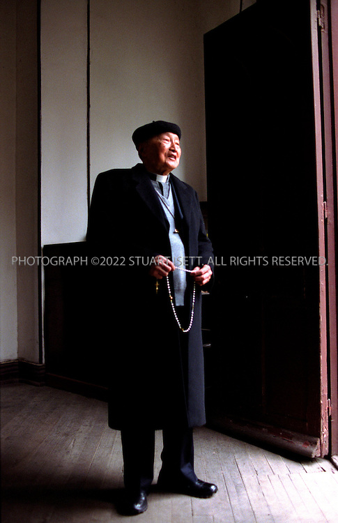 4/28/2004--Shanghai, China..Shanghai's Bishop Aloysius Jin, who leads the 140,000 official Catholics in Shanghai. Bishop Jin, 85, was imprisoned for 27 years, before and during the Cultural Revolution. He was ordained in 1945, studied theology in Europe, and returned to China in 1950. He was arrested in 1955 and did not see freedom again until 1982. The politics of modern China forces him to choose his allegiances: He can pledge loyalty to the pope or to Beijing, but not to both. The Vatican refuses to recognize the government in Beijing, and the government in Beijing ruthlessly suppresses Catholics who remain loyal to the Vatican...Photograph by Stuart Isett.©2004 Stuart Isett