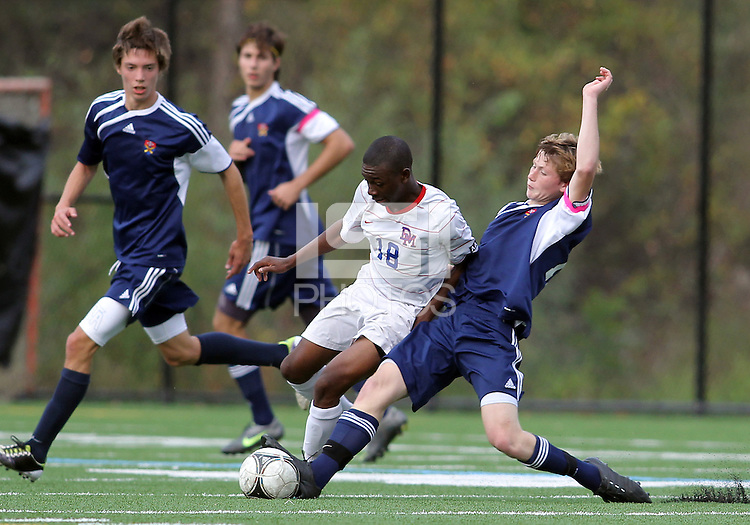 HYATTSVILLE, MD - OCTOBER 26, 2012:  Chris Odoi-Atsem (18) of DeMatha Catholic High School is tackled by Nate Johnson (19) of St. Albans during a match at Heurich Field in Hyattsville, MD. on October 26. DeMatha won 2-0.