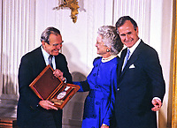 ***FILE PHOTO*** George H.W. Bush Has Passed Away<br /> United States President George H.W. Bush and first lady Barbara Bush present the National Medal of Arts to Polish poet, prose writer, translator and diplomat Czes?aw Mi?osz during a ceremony in the East Room of the White House in Washington, DC on November 19, 1989. CAP/MPI/RS<br /> &copy;RS/MPI/Capital Pictures