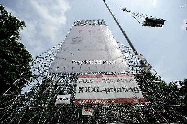 Foto: VidiPhoto..NIJMEGEN - In het Valkhofpark in Nijmegen wordt met steigermateriaal een middeleeuwse donjon van 48 meter hoog nagebouwd. Zodra het gevaarte klaar is wordt het bekleed met gezeefdrukt doek, waarmee een middeleeuwse woontoren wordt gesuggereerd. De toren verrijst op dezelfde plek waar eeuwen geleden de donjon heeft gestaan. De 'herbouw' is een initiatief van de Valkhofvereniging en wordt uitgevoerd door steigerbouwer Jako uit Nijmegen. Op 2 juli wordt de uitkijktoren geopend.