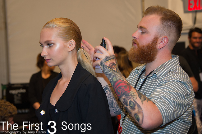 A model prepares backstage at the Custo Barcelona fashion show during Mercedes-Benz Fashion Week Spring 2015 at The Pavilion at Lincoln Center in New York City.