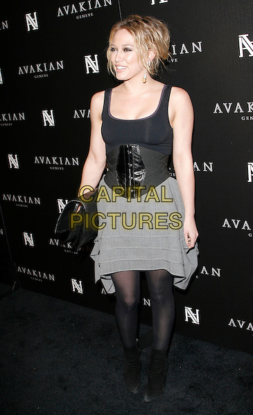 HILARY DUFF .At The Avakian Beverly Hills Boutique Celebrationat Beverly Hills in Beverly Hills, California on December 4th 2008.                                                                     .full length black vest corset belt waist grey gray dress tights clutch bag ankle boots tiered .CAP/DVS.©Debbie VanStory/Capital Pictures