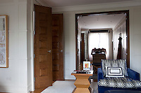 A large mirror dominates one of the wood panelled walls in the bedroom