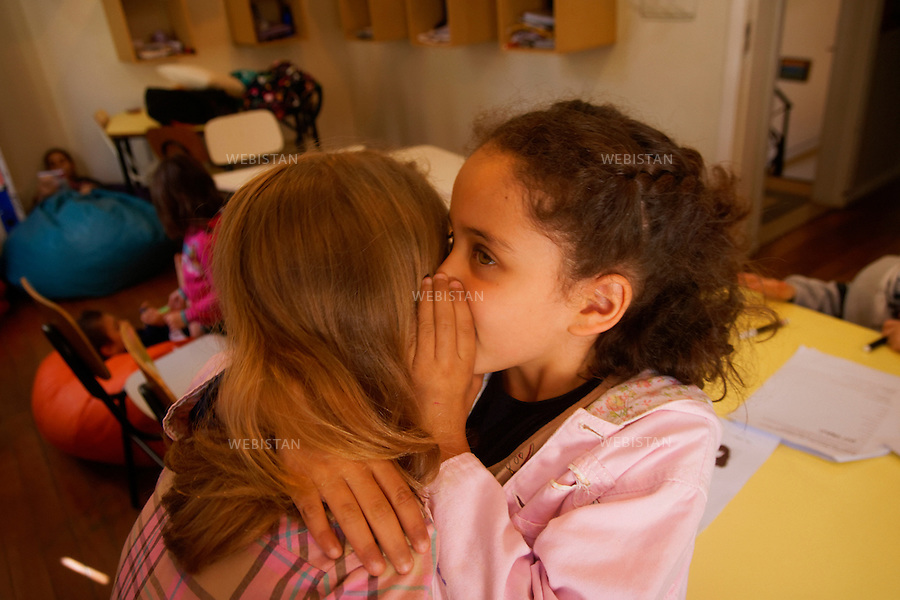Bresil, Sao Paulo, 17 aout 2012..Deux eleves de l'ecole Lumiar partagent un secret...Au Bresil, les ecoles Lumiar proposent une nouvelle forme de pedagogie, proche de celle des ecoles Montessori, ou le temps dedie a l'enfant est reparti entre tuteurs et experts. Une ergonomie innovante de l'espace scolaire, des projets sur mesure, une implication des enfants dans les reflexions et decisions sur leur apprentissage, sont mis en oeuvre pour transmettre differemment savoir et competences...Brazil, Sao Paulo, August 17, 2012..Two students from the Lumiar school share a secret...In Brazil, Lumiar schools offer a new kind of educational methods, similar to the Montessori approach, splitting traditional teaching in two separate roles: the mentor and the master. Knowledge and skills are transmitted in a new way thanks to innovative school place ergonomics, tailor-made projects and the students' involvement in the thinking and decision-making about their own learning...