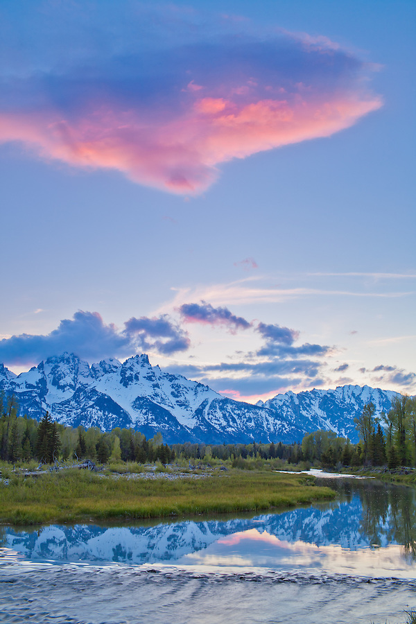 Orange and purple light scatters on the clouds over the Tetons during sunset.