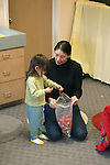 Berkeley CA Asian music teacher getting toddler in music program to help put away rhythm bells at music class