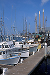 Commercial fishing boats and power plant smoke stacks at Morro Bay harbor, San Luis Obispo County coast, California