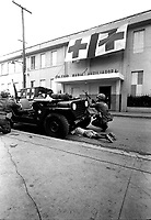 Humanitarian G.I.'s.  Firefight where G.I. pushes little kid under jeep for protection, Santo Domingo, May 5, 1965.  Jack Lartz.  (USIA)<br /> NARA FILE #:  306-DR-2-8<br /> WAR &amp; CONFLICT BOOK #:  378