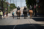 Onlookers watch Portland Police Bureau's Mounted Patrol Unit; Marty Schell, on Major, Appaloosa-Percheron horse, left, Cassandra Wells on Asher, a Percheron, and Melissa Newhard, on Monte, a Belgium quarter horse, ride along the light rail tracks towards the Northwest District.<br /> Photo by Jaime Valdez