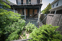 Dilapidated home in the Flatlands neighborhood of Brooklyn in New York on Saturday, June 22, 2013. After being damaged by squatters and a fire the city is deciding whether to tear down the house, but only after numerous complaints from neighbors over the condition of the building. (© Richard B. Levine)