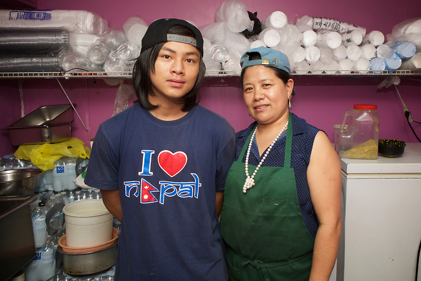Queens, NY - July 10, 2017:  Gyan K. Thapa, owner of Hamro Bhims Cafe, a Nepali restaurant in Jackson Heights, seen here with her son. A family business, her children take orders, prep and plate food and serve diners.<br /> <br /> Credit: Clay Williams for Edible Queens.