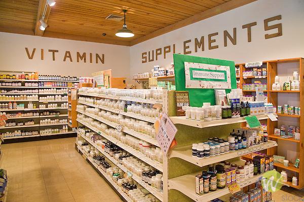 Vitamin supplement bottles on shelves in health store.