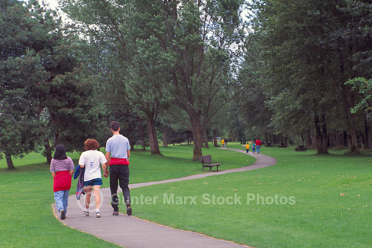 Young People walking on Meandering Path in Burnaby Fraser Foreshore Park along the Fraser River, Burnaby, BC, British Columbia, Canada