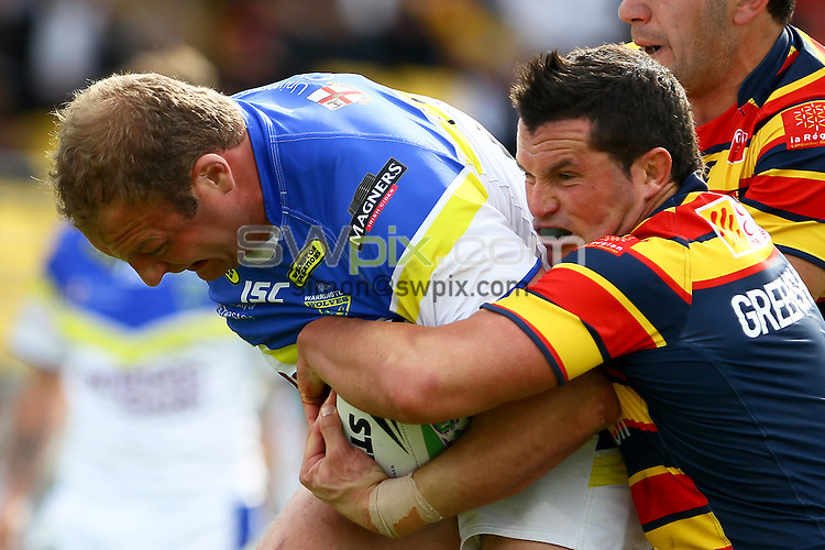 PICTURE BY ALEX WHITEHEAD/SWPIX.COM - Rugby League - Challenge Cup Quarter-Final - Catalan Dragons v Warrington Wolves - Stade Gilbert Brutus, Perpignan, France - 13/05/12 - Warrington's Garreth Carvell tries to escape the tackle of Catalan's Clint Greenshields.