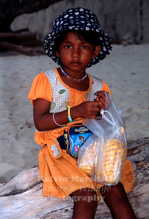 Young Thai girl selling pineapple on the beach. AoNang - Krabi, Southern Thailand.