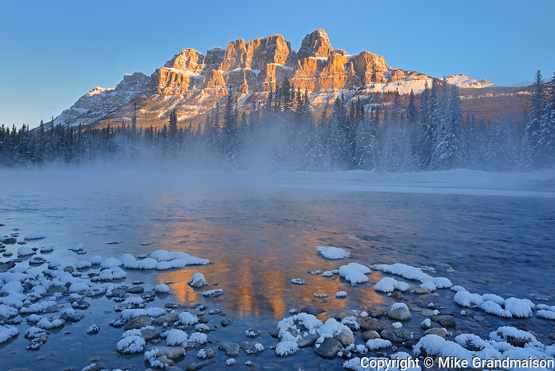 Castle Mountain of the Canadian Rocky Mountains reflected in the Bow River at sunrise. , Banff National Park, Alberta, Canada