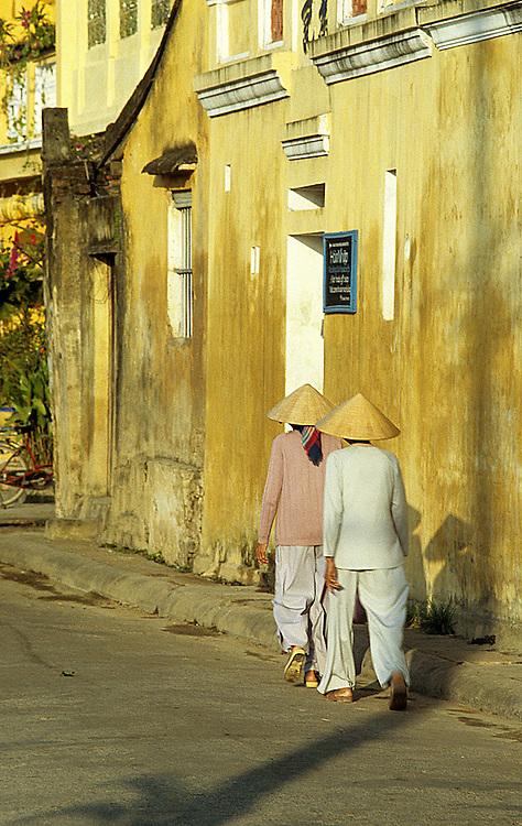 Ochre Wall 02 - Women in conical hats walking along Bach Dang St, early morning, Hoi An, Viet Nam.