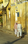 Ochre Wall 02 - Women in conical hats walking along Bach Dang St, early morning, Hoi An, Viet Nam.
