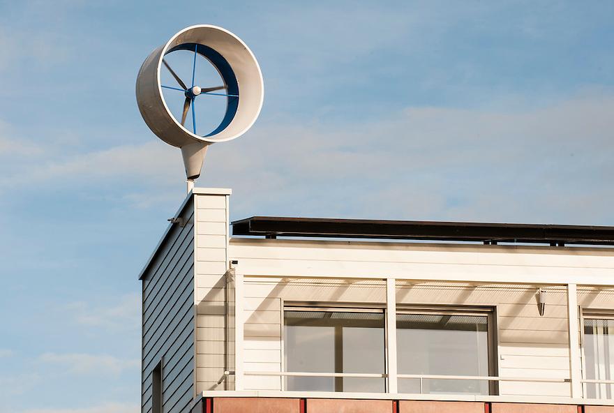 Nederland, Almere, 25 nov 2013<br /> Almere de Poort. Woonhuis met windmolen op dak. Er achter huizen met zonnepanelen.<br /> <br /> Foto: Michiel Wijnbergh
