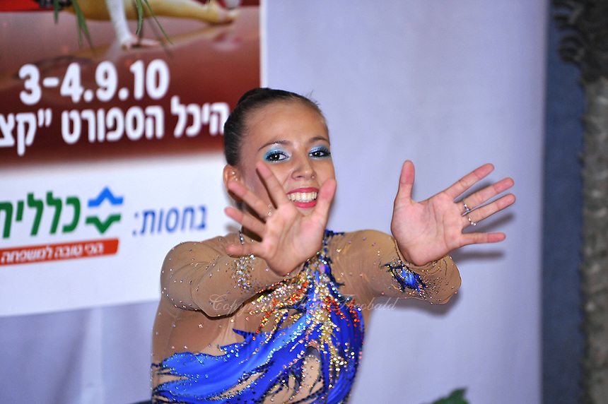 "Daria Dmitrieva of Russia waves to camera from ""kiss & cry"" during event finals at 2010 Holon Grand Prix at Holon, Israel on September 4, 2010.  (Photo by Tom Theobald)"